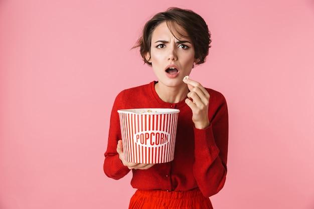Ritratto di una giovane e bella donna confusa che indossa un abito rosso in piedi isolato su sfondo rosa, mangiando popcorn
