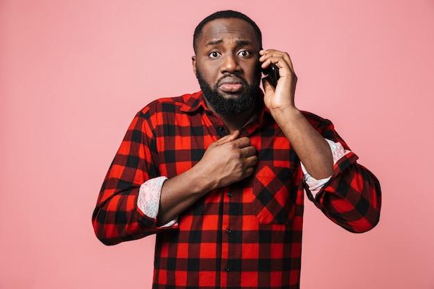 Ritratto di un uomo africano casual confuso in piedi isolato, parlando al telefono cellulare