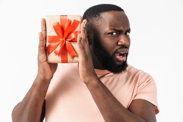 Ritratto di un uomo africano eccitato confuso che indossa una camicia in piedi isolato, mostrando la scatola attuale