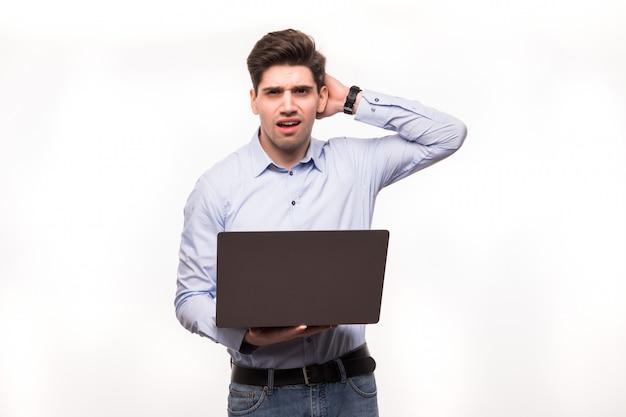 Ritratto di un uomo frustrato confuso in computer portatile bianco della tenuta della camicia mentre gesticolando con la mano isolata sopra spazio bianco
