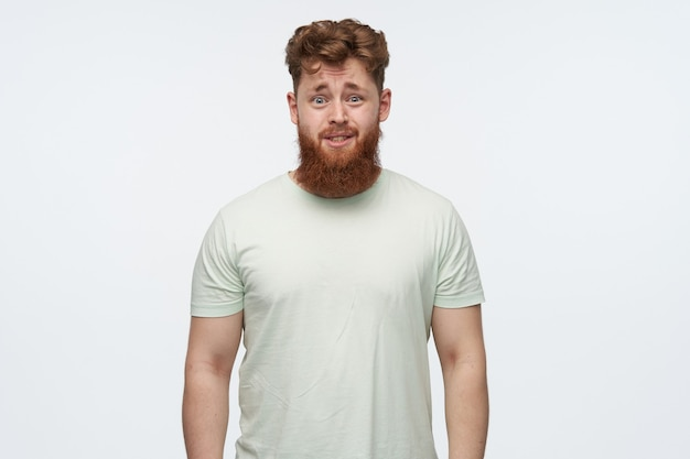 Ritratto di giovane maschio barbuto irritato confuso con capelli rossi, indossa la maglietta in bianco su bianco