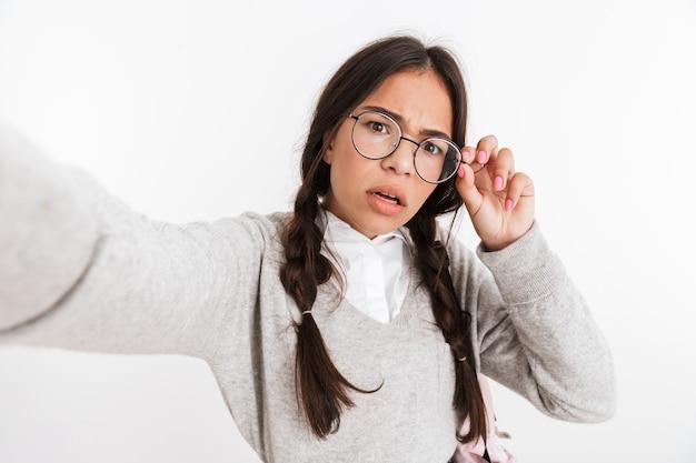 Ritratto di una giovane studentessa seria confusa isolata su un muro bianco in posa per fare un selfie con la telecamera