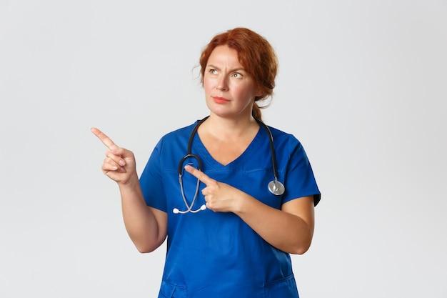 Ritratto di medico di mezza età confuso e scettico rossa, infermiera in camice che punta nell'angolo in alto a sinistra e sembra sospettosa