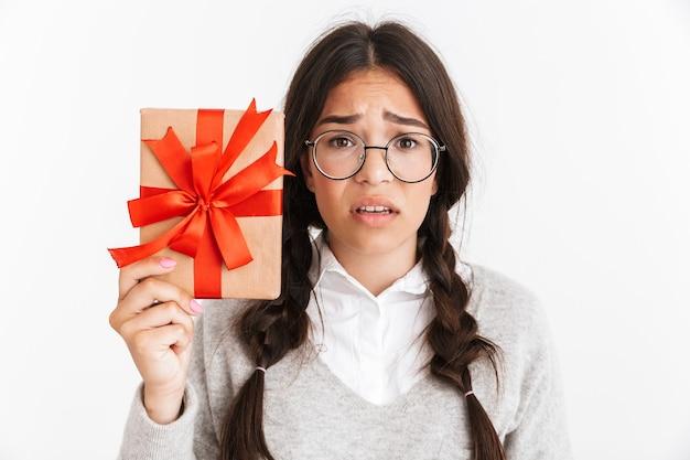Ritratto di giovane studentessa confusa della scuola isolata sopra il muro bianco che tiene il regalo della scatola di sorpresa