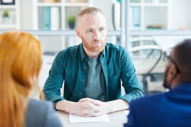 Ritratto di uomo adulto contemporaneo ascoltando i responsabili delle risorse umane durante il colloquio di lavoro in ufficio, copia dello spazio