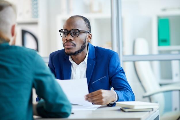 Ritratto dell'uomo d'affari afroamericano contemporaneo che ascolta il candidato durante il colloquio di lavoro in ufficio, lo spazio della copia
