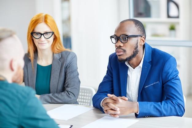 Ritratto dell'uomo d'affari afroamericano contemporaneo che ascolta il candidato durante il colloquio di lavoro in ufficio