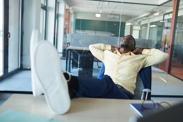 Ritratto di uomo d'affari afro-americano contemporaneo rilassante al posto di lavoro in ufficio con i piedi sulla scrivania, copia dello spazio