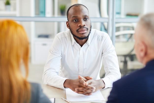 Ritratto dell'uomo afroamericano contemporaneo che ascolta il responsabile delle risorse umane durante il colloquio di lavoro in ufficio, copia dello spazio