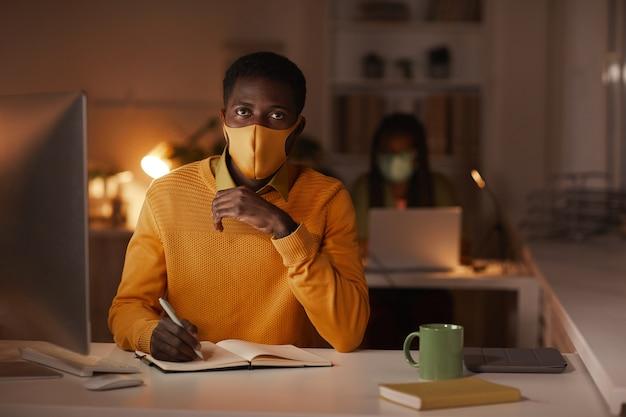 Ritratto di uomo afro-americano contemporaneo che indossa la maschera in ufficio e guardando la fotocamera mentre si lavora a tarda notte, copia dello spazio