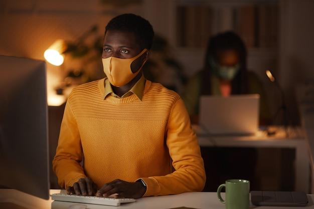 Ritratto di uomo afro-americano contemporaneo che indossa la maschera in ufficio mentre si lavora a tarda notte illuminato dalla luce del laptop, copia dello spazio