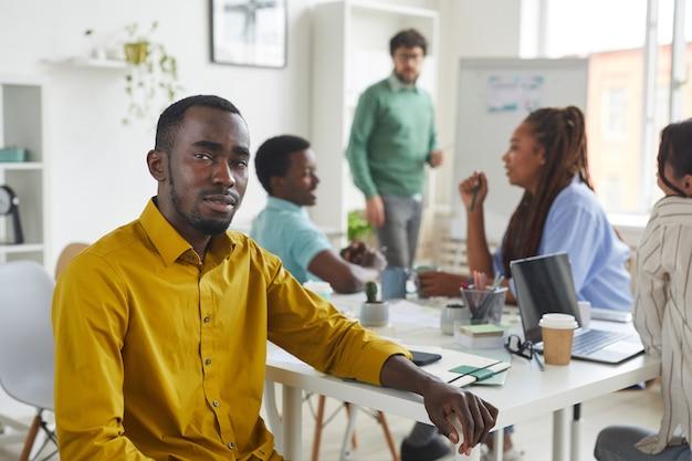Ritratto di uomo afro-americano contemporaneo mentre era seduto al tavolo durante la riunione con la squadra di affari