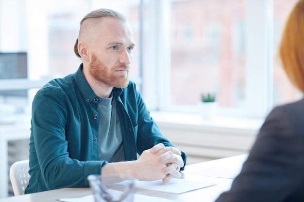 Ritratto di uomo barbuto contemporaneo ascoltando il responsabile delle risorse umane durante il colloquio di lavoro in ufficio, copia dello spazio