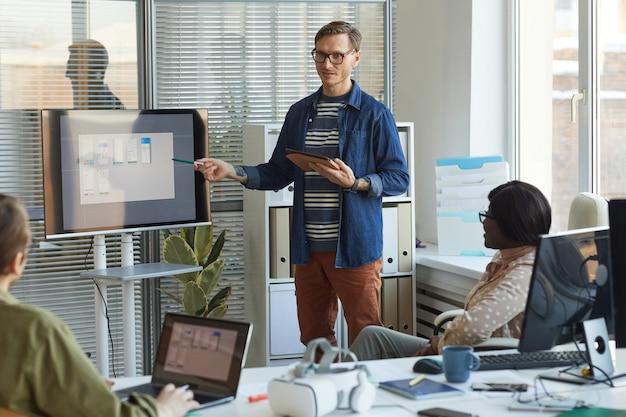 Ritratto di uomo d'affari contemporaneo che punta allo schermo digitale mentre fa una presentazione alla riunione del team nell'ufficio di produzione del software, spazio di copia