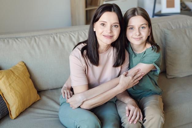 Ritratto di madre bruna contenuto seduto sul divano e abbracciando figlia adolescente a casa