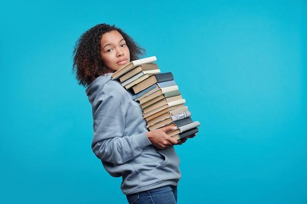 Ritratto di ragazza studente nero dai capelli ricci contenuto che trasportano grande pila di libri su sfondo blu, preparando per il concetto di esame