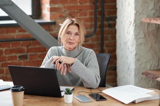Ritratto del capo della signora contenuto in maglione grigio seduto alla scrivania con il computer portatile in ufficio moderno loft