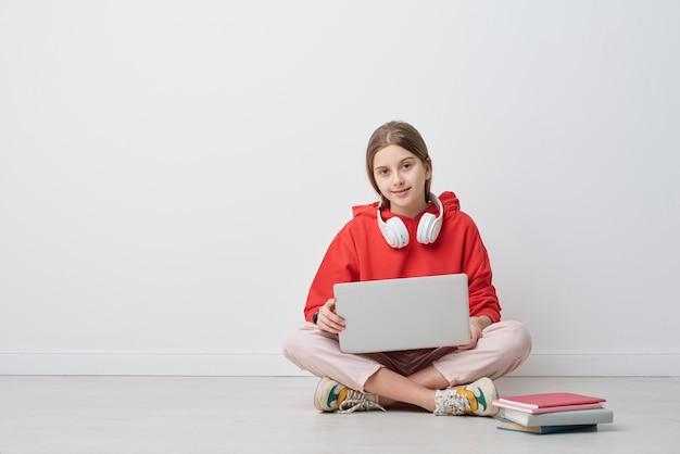 Ritratto di ragazza di liceo moderno contenuto in felpa con cappuccio rossa seduta con le gambe incrociate sul pavimento e utilizzando il computer portatile