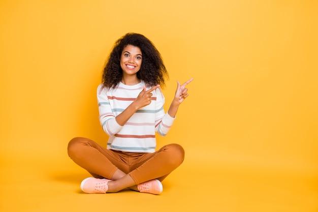 Ritratto della ragazza dai capelli ondulati contenuto che si siede nella posa del loto che indica da parte