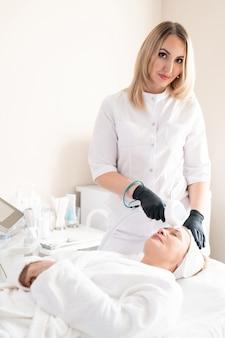 Ritratto di contenuto giovane cosmetologo in guanti chirurgici utilizzando un dispositivo di bellezza per pulire la pelle della donna matura