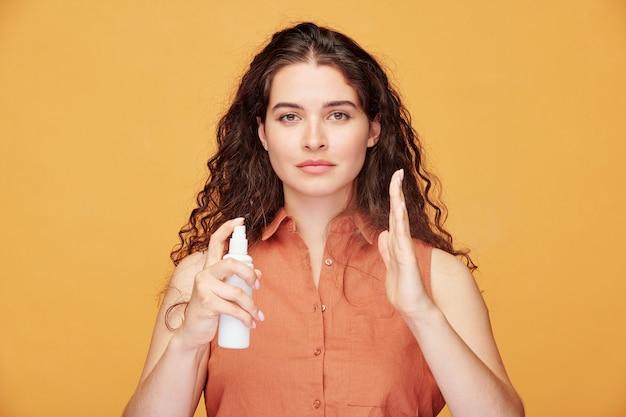 Ritratto di giovane donna soddisfatta con capelli castani che spruzza le mani con disinfettante mentre pratica l'igiene delle mani durante l'epidemia di coronavirus