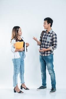 Ritratto di conversazione amici del college che trasportano una borsa e un libro su sfondo bianco