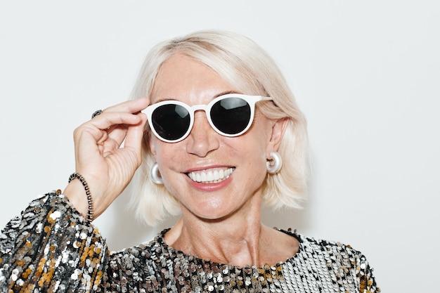 Ritratto di una bella donna matura che indossa un abito glamour e guarda la telecamera contro il muro bianco, ripresa con il flash