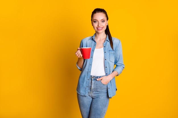 Ritratto di bella ragazza carina tenere una tazza con latte caldo godersi la pausa del tempo libero indossando abiti in stile casual isolati su uno sfondo di colore brillante