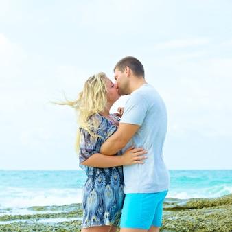 Ritratto di una coppia in abbigliamento casual che si bacia sulla spiaggia in estate