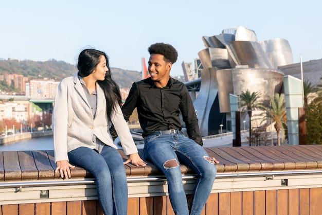 Ritratto di una coppia di una ragazza caucasica e un ragazzo marocchino con capelli afro molto felici e si guardano con complicità seduti in visita a bilbao