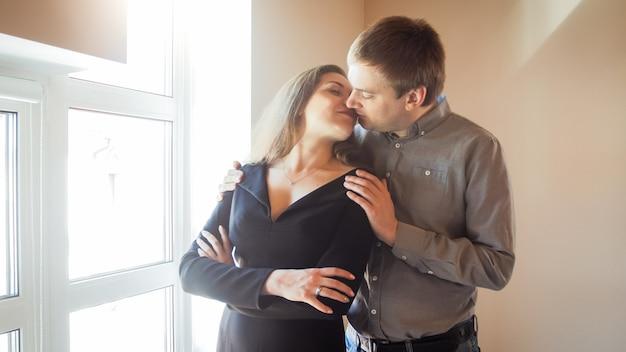Ritratto di coppia innamorata che si bacia e si abbraccia alla finestra della loro casa
