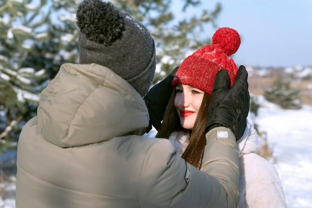 Ritratto di coppia innamorata in inverno all'esterno. guy raddrizza il suo amato cappello da ragazza.