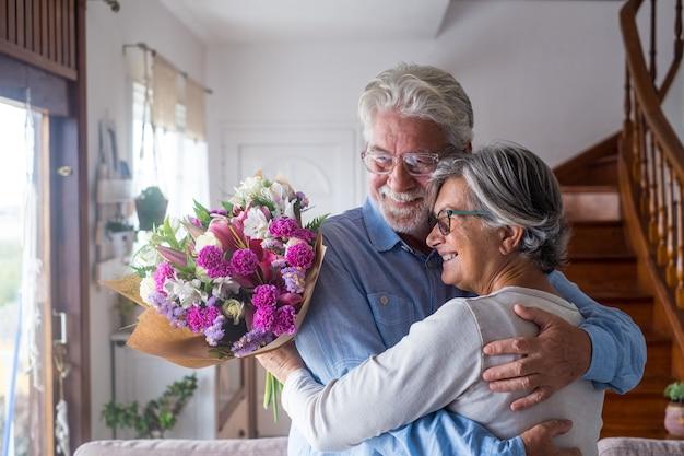 Ritratto di coppia di due anziani felici e innamorati o persone mature e anziane che tengono fiori a casa guardando fuori. pensionati adulti che si godono e celebrano le vacanze insieme.
