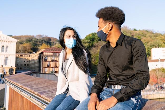 Ritratto di una coppia di giovani amici seduti in una città per strada con maschere facciali a causa della pandemia di coronavirus covid-19