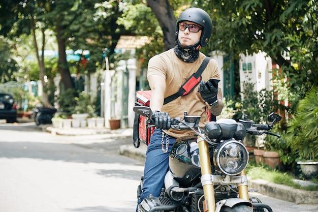 Ritratto di corriere in moto che si guarda intorno alla ricerca della casa del cliente