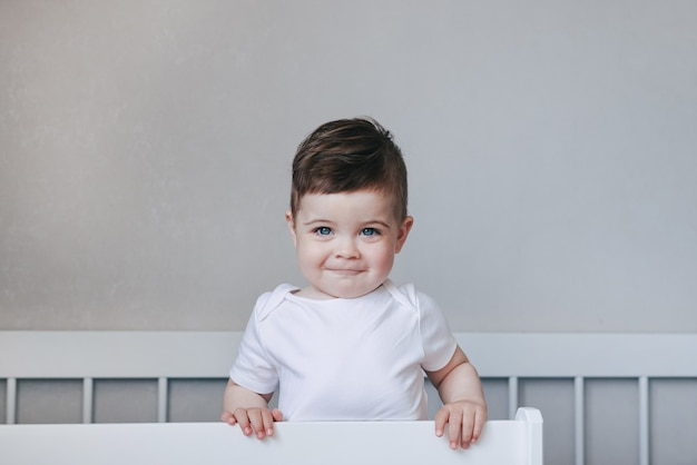 Ritratto di un bambino strisciante e sorridente in tuta bianca sul letto in camera da letto. grandi occhi blu. concetto di infanzia felice con copyspace