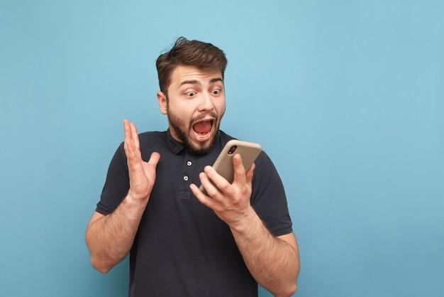 Ritratto di un pazzo uomo barbuto con uno smartphone in mano, guardando lo schermo e urlando sull'azzurro