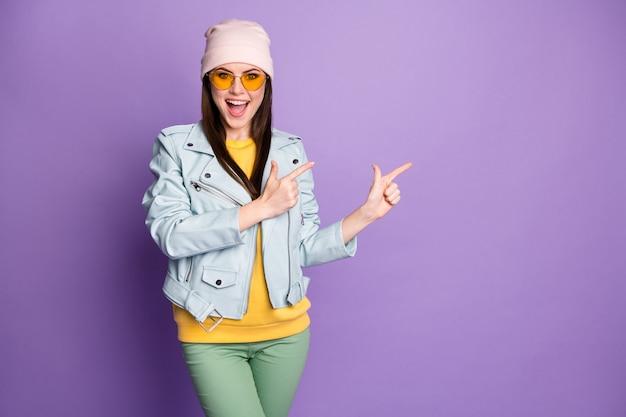 Ritratto di ragazza pazza allegra promotore punto dito indice copyspace annunci di vendita incredibili promozione display consigliare scegliere decidere indossare abiti di bell'aspetto isolato sfondo di colore viola
