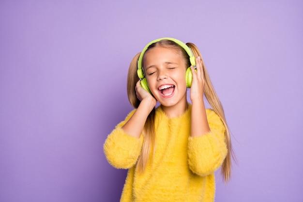 Ritratto di bambino funky pazzo utilizzare auricolare verde ascoltare musica radiofonica cantare canzone indossare pullover stile casual isolato sopra la parete di colore viola