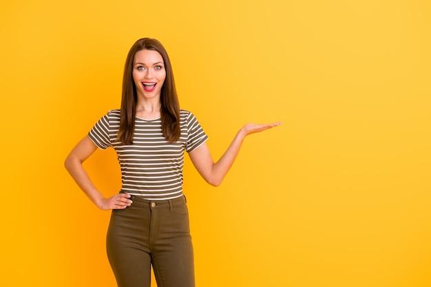 Ritratto di crazy funky girl promotore tenere per mano presente annunci promozionali meravigliosi urlare wow omg consiglia di raccogliere suggerimenti indossare un bell'aspetto isolato su parete di colore giallo
