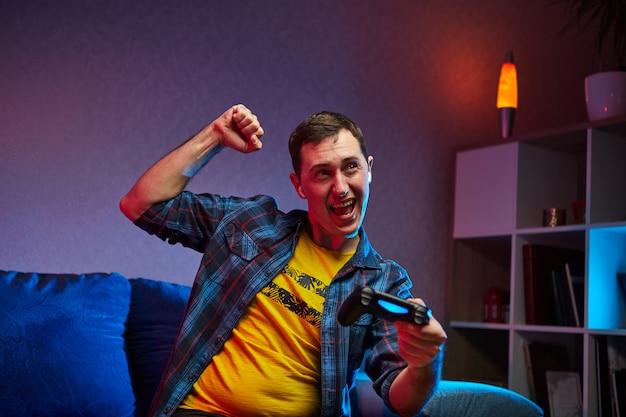 Ritratto del pazzo giocoso giocatore che si diverte giocando ai videogiochi