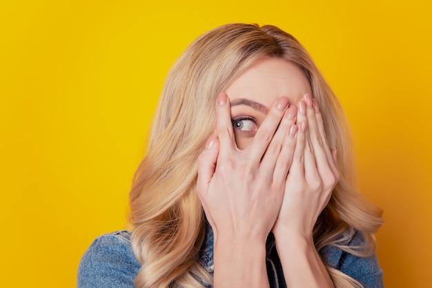 Il ritratto delle mani della ragazza bionda scioccata pazza copre gli occhi sembra uno spazio vuoto su sfondo giallo