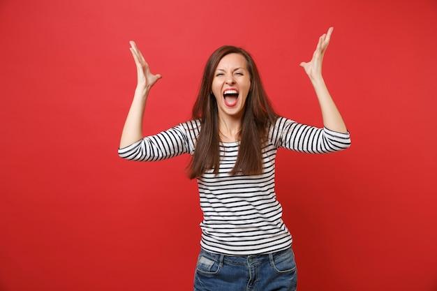 Ritratto di una giovane donna pazza in abiti casual a righe che urla, si alza e allarga le mani