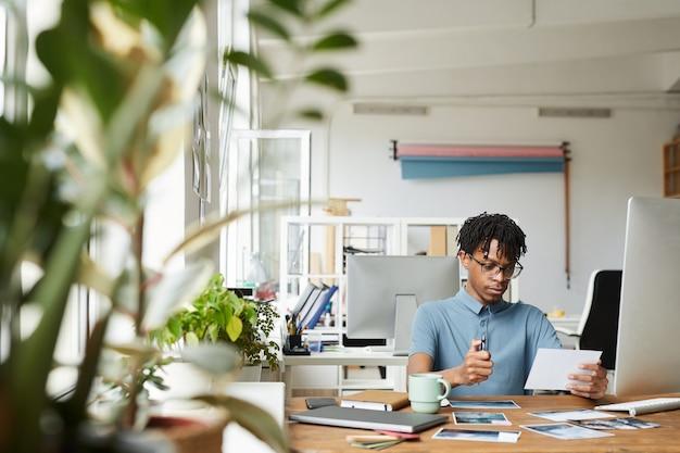 Ritratto dell'uomo afroamericano creativo che esamina le fotografie mentre lavora alla modifica e alla pubblicazione in ufficio moderno, spazio della copia