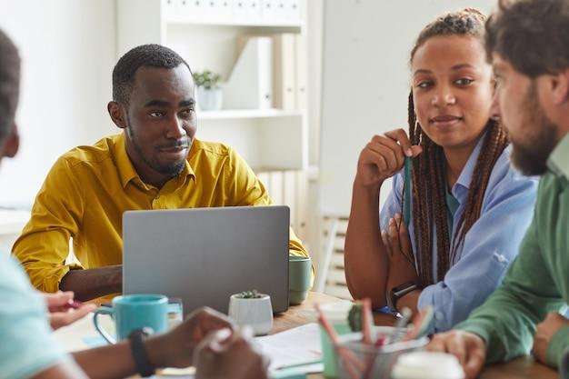 Ritratto di uomo afro-americano creativo utilizzando laptop mentre si lavora al progetto di squadra con un gruppo multietnico di persone