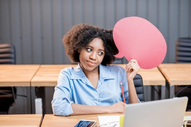 Ritratto di donna d'affari creativa di etnia africana seduta con fumetto pensiero in ufficio