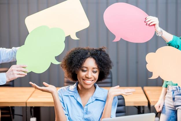 Ritratto di donna d'affari creativa di etnia africana seduta con bolle di pensiero in ufficio