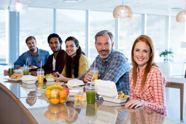 Ritratto di team creativo di affari che mangia in ufficio