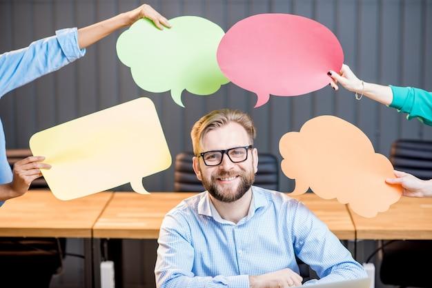 Ritratto di uomo d'affari creativo seduto con bolle di pensiero in ufficio