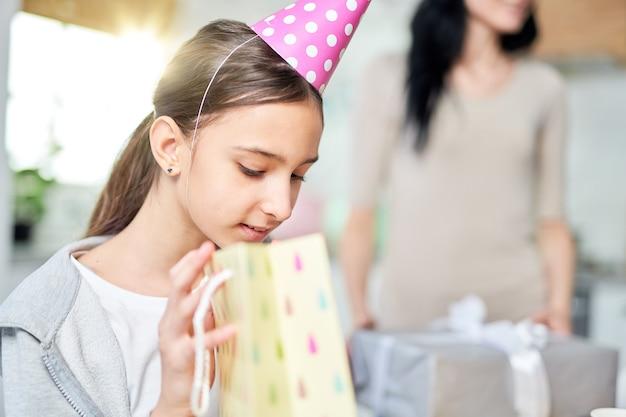 Ritratto di curiosa ragazza latina adolescente che controlla la borsa regalo, mentre riceve regali, festeggia il compleanno con i genitori a casa. celebrazione, concetto di infanzia